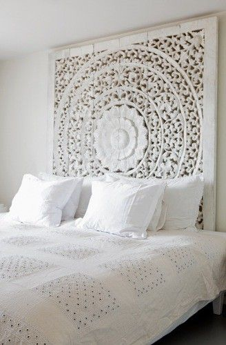 White bedroom with an unique headboard..