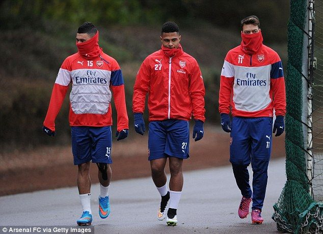 Alex Oxlade-Chamberlain, Serge Gnabry and Mesut Ozil walk to the pitch before training on ...