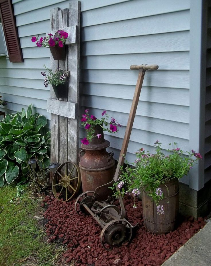 Rustic Garden Display of a Vintage Push Mower, Milk Can, Crock, and Door