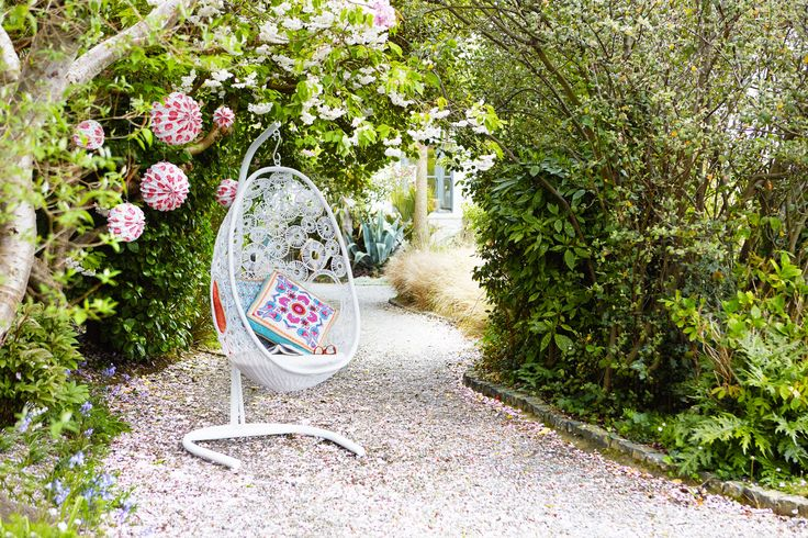 White outdoor chair with cushions and paper lanterns, all Carolyn Donnelly eclectic