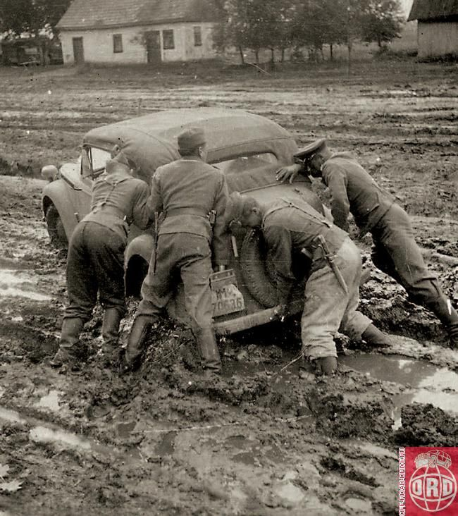 Russian roads WW2. German soldiers and officers are pushing a car stuck in the Russian mud.