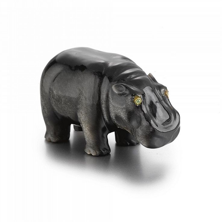 A CARVED OBSIDIAN FIGURE OF A HIPPOPOTAMUS, CIRCA 1900 depicting standing on four legs, set with olivine eyes  possibly by Fabergé length 1 3/4 in. 4.5 cm