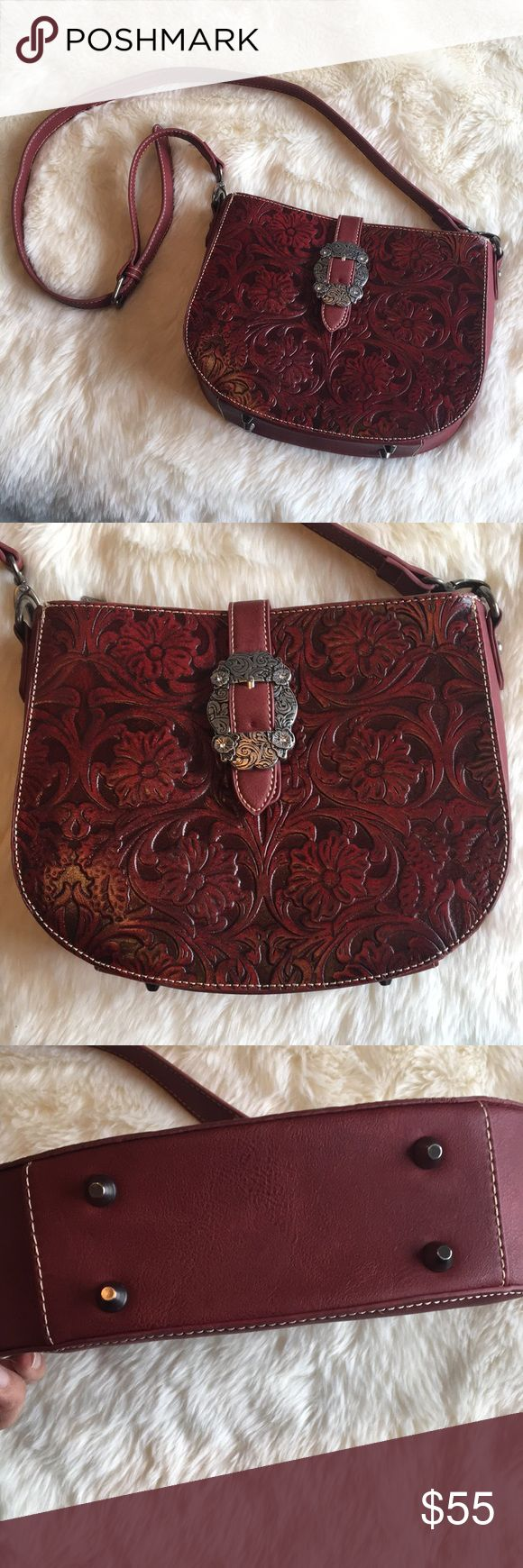 Trinity Ranch red leather shoulder/crossbody bag Trinity Ranch line by Montana West, this partial leather handbag has:  Floral tooled design on genuine leather buckle concho on the flap that snap close A single compartment divided by a medium zippered pocket A smaller zippered pocket on inside back 2 open pockets on the inside front Single flat straps  10.5 x 3 x 9 (23 drop strap)  Excellent preloved condition, no flaws Trinity Ranch Bags