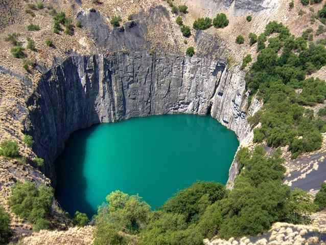 """Кимберлитовая трубка """"Большая дыра"""", ЮАР Глубина - 214 метров """"Большая дыра"""" является недействующим алмазным рудником, который закрылся в 1914 году. Сейчас она представляет собой огромный кратер, наполненный водой, периметром 1,6"""