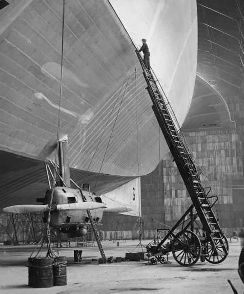 "r0llerdisc0:  my-ear-trumpet:  xplanes:  ""HM Airship R100 nears completion at the Royal Naval Air Service Air Station near Howden in Yorkshire, November 1929. An extendable fire ladder is used to put the finishing touches to the linen fabric of the giant craft, covering it with a layer of aluminium aircraft dope."" (very little remains of the station and sheds/hangars today)"