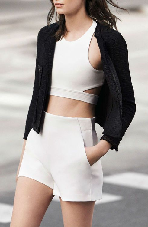 Acheter la tenue sur Lookastic: https://lookastic.fr/mode-femme/tenues/veste-boucle-top-court-blanc-short-blanc/2309 — Top court blanc — Veste bouclé noire — Short blanc
