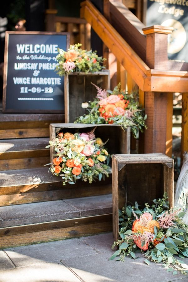 Soft greens and oranges accent the wood decor of this rustic wedding.
