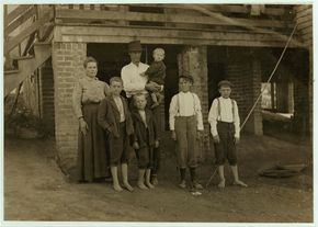 "S.D. Ison and family. Father works some. Both boys on right of photo have been in Washington Cotton Mills, Fries, Va., for four years. When I asked the smallest worker how old he was, he said, ""Don't know,"" and looked at his father, who said, ""Going' on 14."" (but he did not say how near to 14 he was). Location: Fries, Virginia."