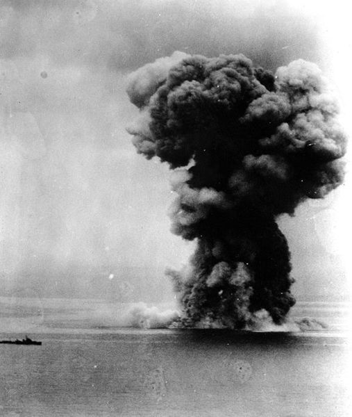 Japanese battleship Yamato blows up, following massive attacks by U.S. Navy carrier planes north of Okinawa, 7 April 1945. An escorting destroyer is at left.  Photographed from a USS Yorktown (CV-10) plane
