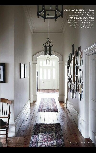 Like - hallway with grand door and picture gallery, worn, wide floorboards.