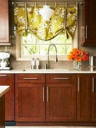 Decorative Details Oversize hardware, a rich cherry finish on the cabinetry, and a glass tile backsplash create an upscale look in this kitchen. A bright floral window treatment adds a refreshing splash of color in an otherwise neutral space. Below, a large stainless-steel sink and commercial-look faucet are perfect for gourmet cooking.