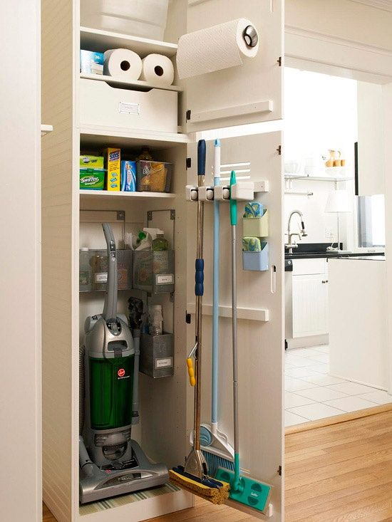 CLEANING CLOSET: finding a place to store cleaning supplies can be challenging, especially if storage space is limited. narrow closet nook corrals essential supplies near the kitchen. small bins organize bottles and brushes, and a door -mounted holder secures taller tools.