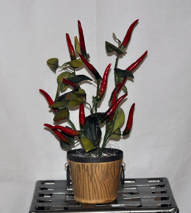This artificial silk red colored Peppers is in a decorative Metal Container and would brighten up a window ledge or place in the kitchen to inspire your cooking!