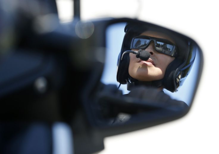 Garden Grove Police Department's Katherine Anderson is reflected in the mirror of her BMW motorcycle. Photo by Christine Cotter