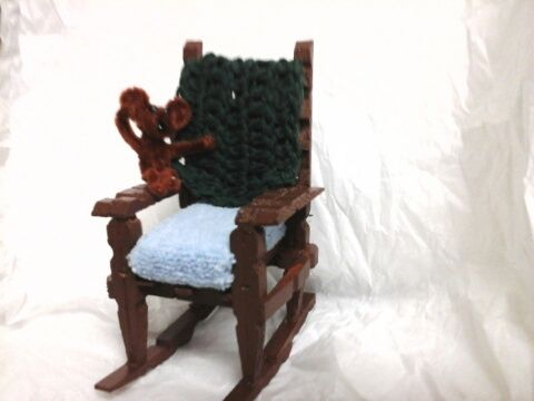 Clothes peg rocking chair with a pipe cleaner bear and a crochet blanket.