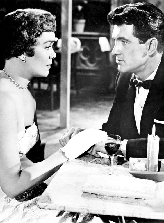 "Jane Wyman & Rock Hudson in Douglas Sirk's, ""Magnificent Obsession', 1954 - After the death of Helen Phillips' (Jane Wyman) husband, Bob Merrick learns about Dr. Phillips selfless, yet secretive help he'd given people & Merrick tries to emulate Dr. Phillips, but in a ham handed way. The result is, he alienates Helen Phillips, who at this point Merrick has fallen in love with."