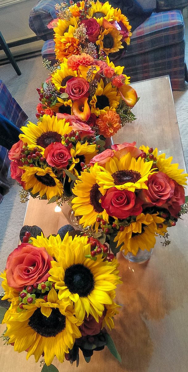 These lovely bouquets for the wedding party were created with burnt orange roses, dahlias, sunflowers, burgundy hypericum berries and calla lilies along with special botanicals and fall greenery.