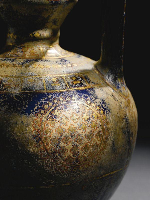 ابریق لاجورد، سفال، اواخر قرن 13 یا اوایل قرن 14 میلادی، ارتفاع 27.5 سانتیمتر A LAJVARDINA POTTERY EWER, PERSIA, LATE 13TH/EARLY 14TH CENTURY the frit body of pear-shaped form with thin neck and wide cylindrical moulded cup, with strap handle, the underglaze cobalt-blue ground decorated with red, white and gold leaf geometric designs over the glaze including roundels containing quatrefoils, ferns, and diamond-shape bands 27.5cm. heigh