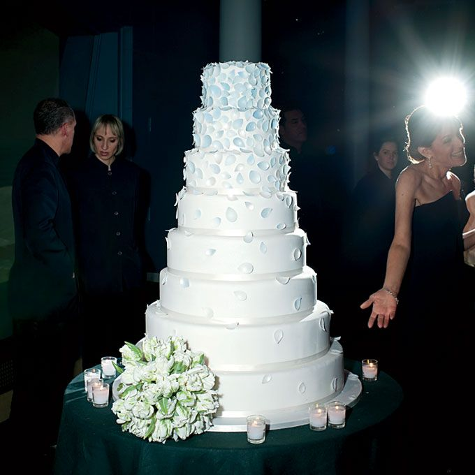 """Brides.com: A Modern, Black-Tie Wedding in New York, NY. The cascade of fondant rose petals on the white wedding cake was inspired by the bride's gown. The cake-cutting song was """"Good Life,"""" by One Republic. Browse more white wedding cakes"""