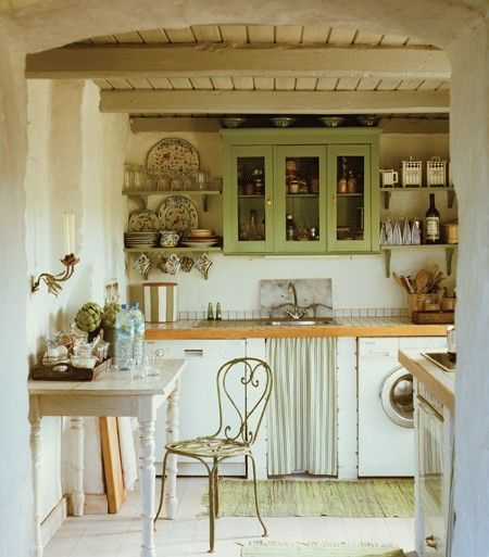 Chicken-wire cabinets keep this look casual. Pretty canisters and open shelving keep everyday items neatly on display. The homeowner is fond of rag rugs — a traditional Swedish element — and uses them here to highlight the green and white colour scheme.