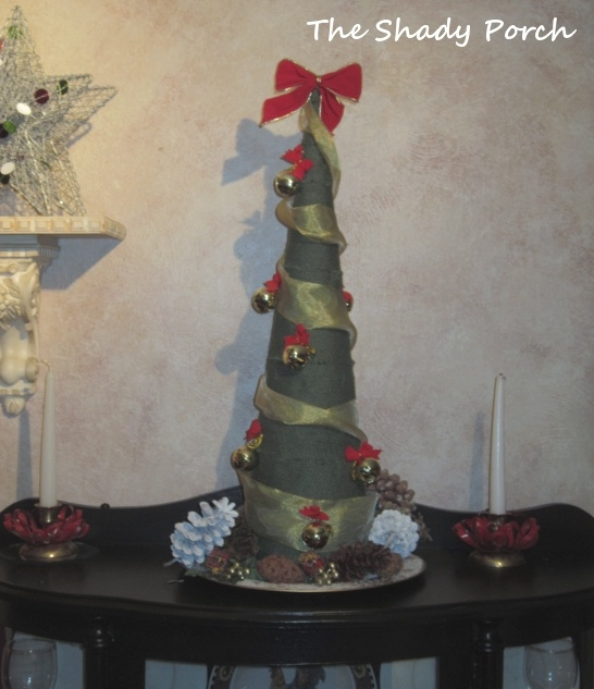 Green Burlap Cone Tree with ribbon, bows and bells.