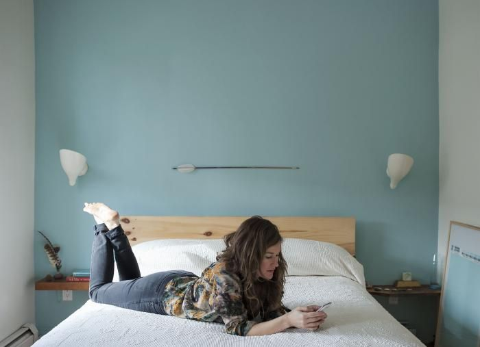 """The architect Jen Turner in her bedroom on the second floor of the carriage house. """"On the feature walls and floors, I splurged with Farrow & Ball and used Benjamin Moore for the rest of the house,"""" she say. """"The Farrow & Ball Blue Ground makes the room feel like it is in a cottage by the sea; a happy blue which is wonderful to wake up to."""""""