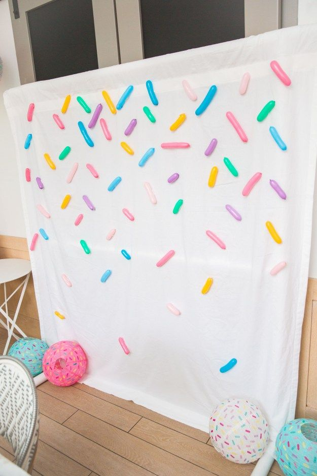 Sprinkles Backdrop for a photo booth. Super easy to make with a white sheet and balloons. I DIY party decorating idea that even the non-crafty can make! A fun idea for a Donut Party.