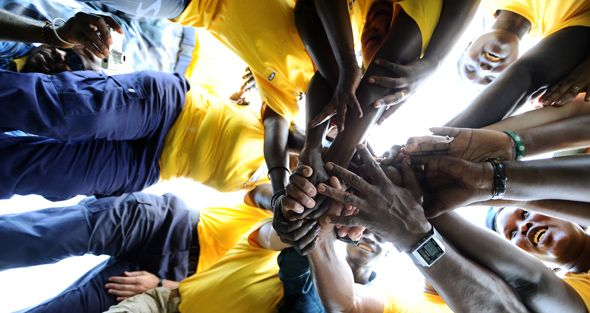 Members of UN Police and South Sudan Police Services hold hands in camaraderie while taking part in a rope pulling competition, during celebrations marking the International Day of Peace.
