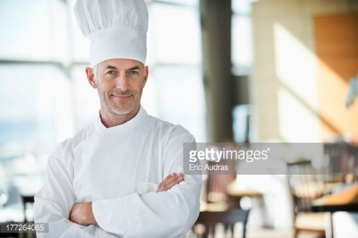 Stock Photo : Portrait of a chef smiling with arms crossed in a restaurant