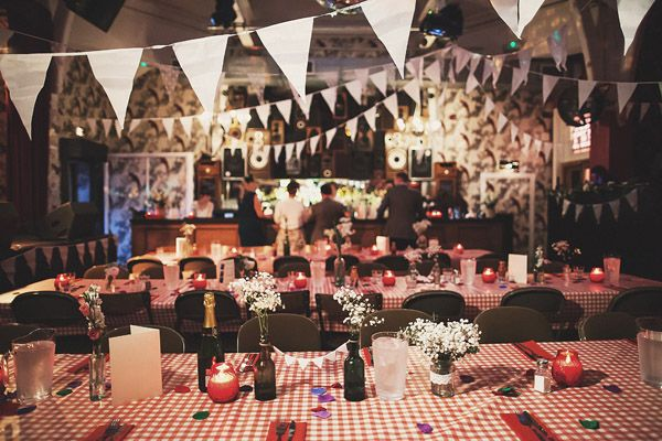 Red gingham tablecloths cover long tables at a quirky, casual and cool wedding
