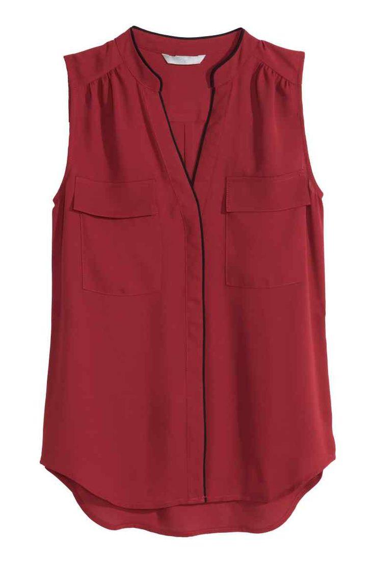 Blusa sin mangas: Blusa de tela sin mangas con detalles en color de contraste. Escote de pico y cierre oculto de botón en la parte delantera, bolsillos superiores con solapa.
