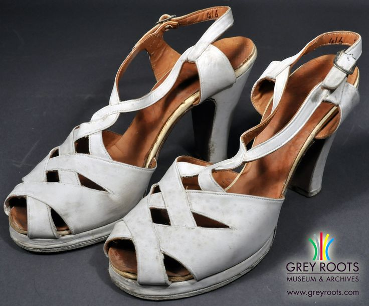 """A pair of ladies', white leather, """"Lady Edna"""", high-heeled shoes. The shoes are strappy and open-toed. The shoes fasten around the ankle with a strap and buckle. They were likely intended for daytime wear. Grey Roots Museum & Archives Collection."""