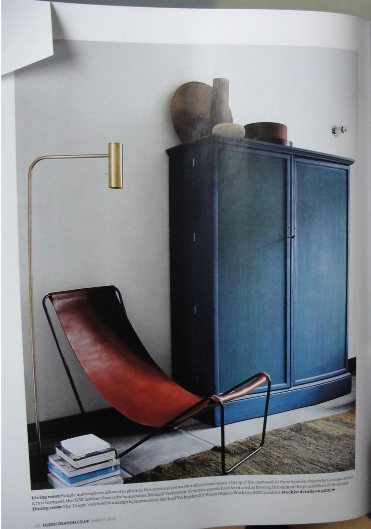 Dark teal cabinet, brass lamp and leather armchair