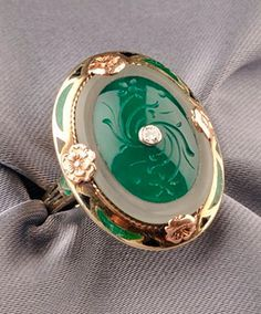 Art Deco 14kt Gold, Chalcedony, and Enamel Ring, centering a carved chalcedony tablet set in a frosted rock crystal frame, diamond melee accent, border and shoulders with enamel reserves,