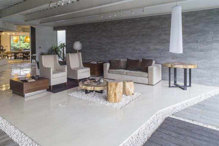 Sillones individuales con y sin brazos con funda.  Mesa auxiliar de Nogal con zoclo de acero.  Pedestales, mesa central y mesa lateral derecha de madera petrificada pulida.