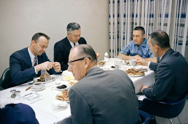 At the head of the table on launch morning, Gus Grissom looks serious ahead of becoming the first man to journey into space twice. Fellow as...