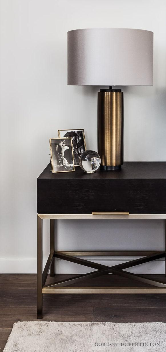 Dark oak and bronze bedside table in master bedroom. Brass lamp with silk shade.