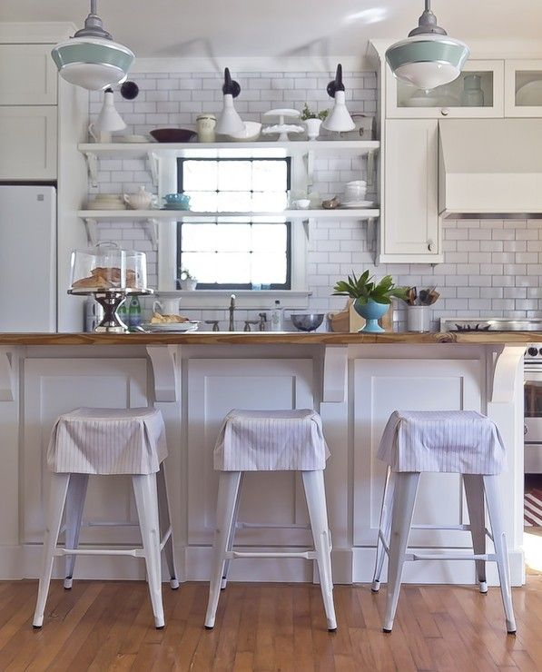 White cottage kitchen with large kitchen island with corbel supports below a butcher block countertop illuminated by a pair of striped schoolhouse pendants with white Tabouret stools tucked below the counter.