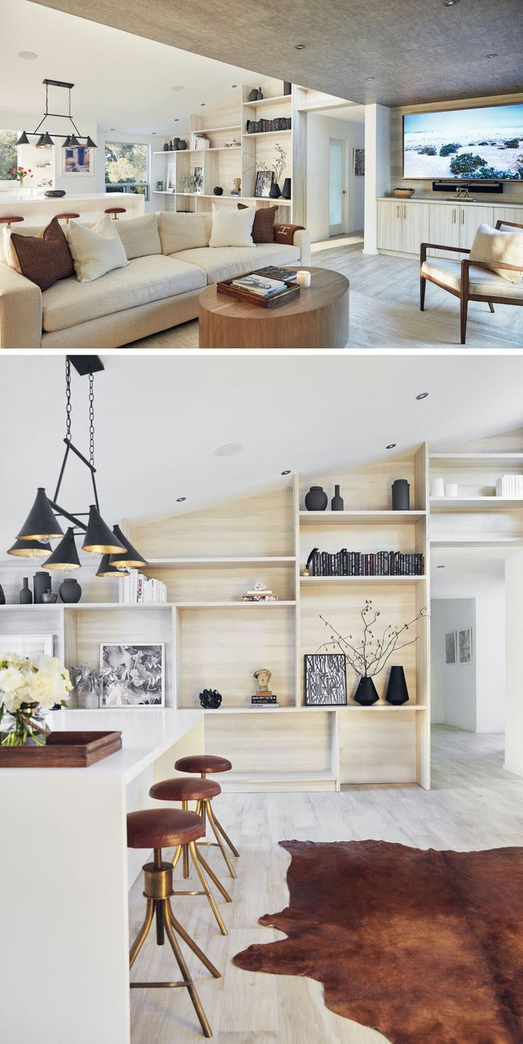 In this home, the main living and kitchen area share the space, with one of the walls covered in light wood shelving, ideal for displaying personal items.