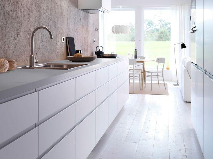 Eine weiße Küche mit NODSTA Türen in Weiß/Aluminium, weißem Fußboden und grauer Betonwand