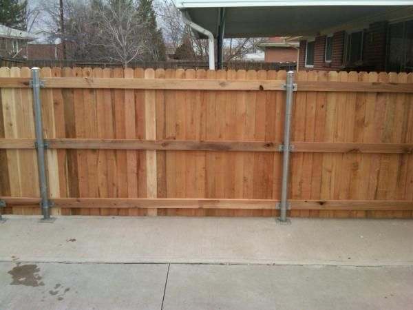 Can new wood fence go over a raised concrete slab