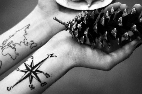 Pequeños tatuajes en los antebrazos de un mapamundi y de la rosa de los vientos con los cuatro puntos cardinales y los cuatro rumbos laterales.