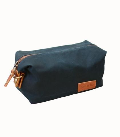 Gouache - Sweeney Toiletry Bag Sea Green Waxed Canvas. Classy and durable, the Sweeney Bag will be one of your go-to essentials for years. Made of water-repellant waxed canvas and featuring an easy-to-clean interior, this gorgeous piece combines form and function seamlessly. If you're looking for a unique, minimalist bag that fills you up with pride, you've found it. Use it for your toiletry essentials or craft supplies – either way, you'll love it. Handmade by displaced artisans in the…