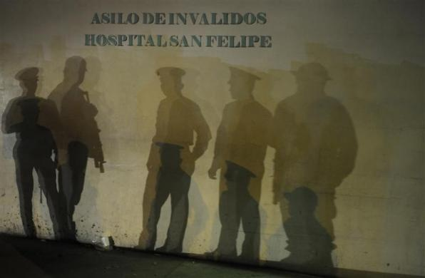 The shadows of police cadets standing guard are cast on a wall with the writing 'Asylum for Invalids San Felipe' in downtown Tegucigalpa, Honduras, December 3, 2012. REUTERS Jorge Cabrera