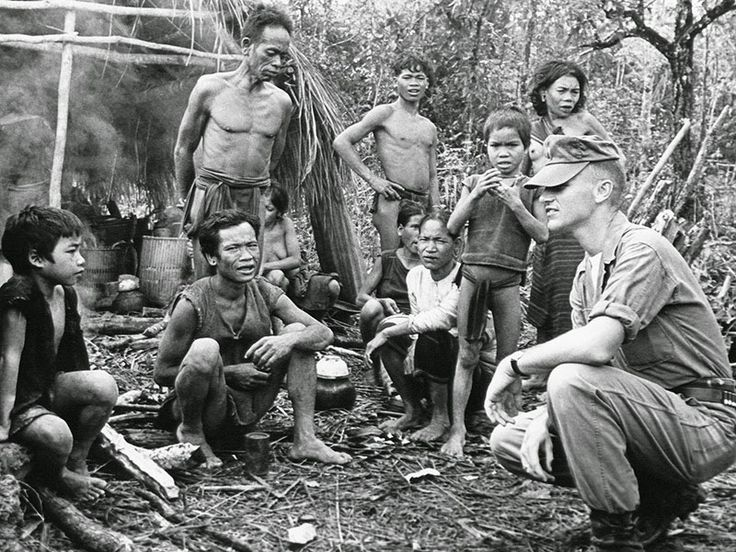An American officer serving with the South Vietnam forces poses with group of Montagnards in front of one of their provisionary huts in a military camp in central Vietnam on November 17, 1962. (AP)