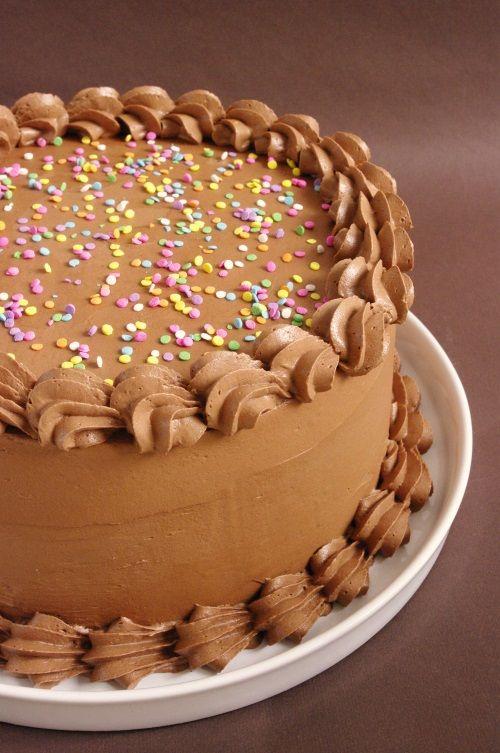 Un layer cake Nutella avec des couches de gâteau à la noisette et un glaçage au Nutella.