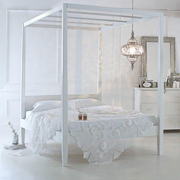 Witte slaapkamer met hemelbed en oosterse zilveren lamp.