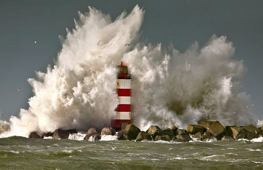 Wave crashing against lighthouse, Ijmuiden, The Netherlands (© frans lemmens/Alamy)