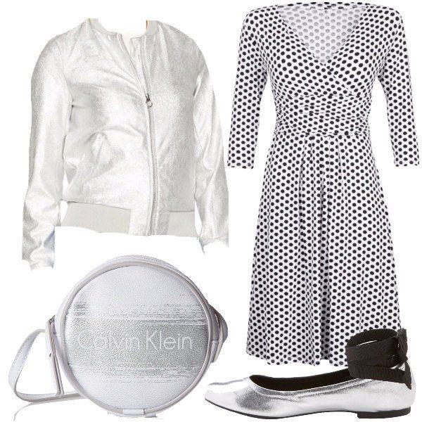 Outfit che vede al centro dell'attenzione un abito in stile anni '50 bianco a pois neri e manica a 3/4. L'abito però, per renderlo più originale, viene accompagnato da un bomber in silver. Il look si completa con un paio di ballerine argentate e lacci neri da legare attorno alla caviglia e da una borsa a tracolla rotonda, anche lei in silver.