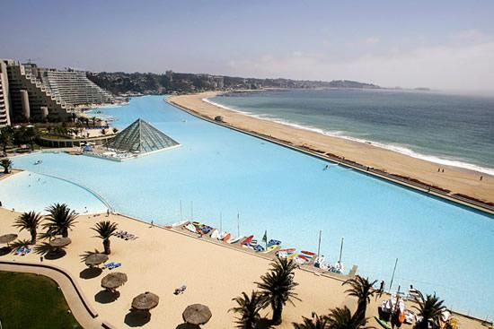 This man-made wonder is 1013 meters long covers 80 acres, its deepest end reaches 115ft and it holds 66 million gallons of water. If you want to take a dip in the world's largest swimming pool you'll have to travel to San Alfonso del Mar in Algarrobo, Chile, where a computer-controlled suction and filtration system continuously pumps water from the ocean, keeping crystal clear.